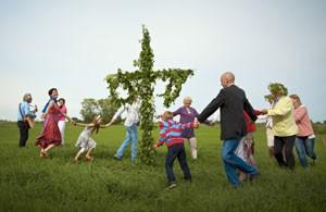 Schweden tanzen zu Mittsommer um die Mittsommerstange.