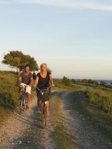Fahrradtour in Schweden, 2 lachende Menschen auf Fahrrädern im Sonnenschein
