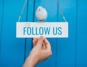 """Türschild mit Aufschrift: """"Follow us"""" Darauf sitzt ein Vögelchen."""