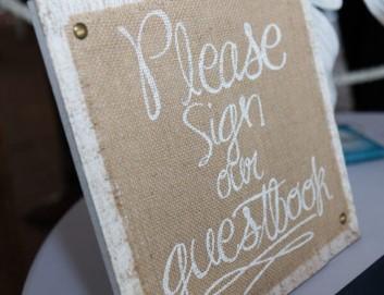 """Strassenschild mit Aufschrift: """"Sign our Guestbook"""""""