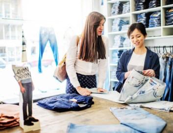 Schwedische Näherei oder Jeansshop, Zwei Frauen in Schweden unterhalten sich über einen Stoff