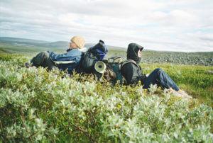 Naturschutz in Schweden - Wanderer sitzen gemeinsam im hohen Gras