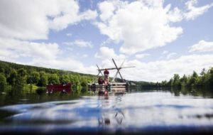 Landschaft in Schweden, mit Bach, viel grün und Windmühle im Hintergrund