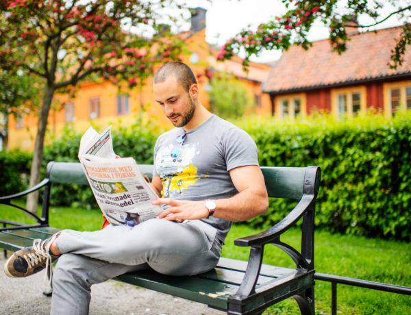 Mann liest Zeitung auf Parkbank